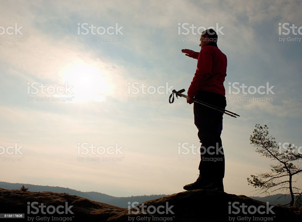 Tourist in windcheater with sporty poles in hands on mountain stock photo