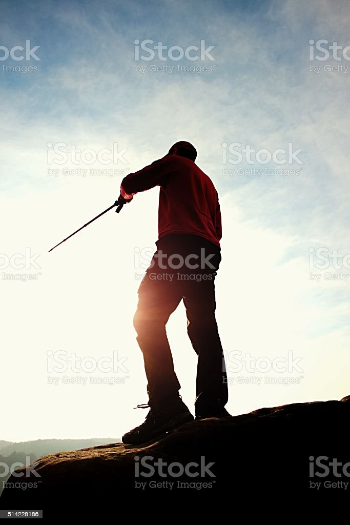 Tourist in windcheater with sporty trecking  poles in hand stock photo