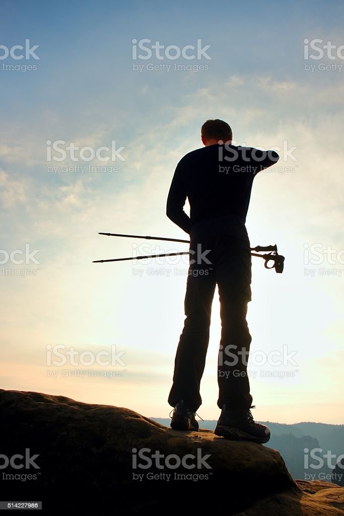 Tourist in windcheater with trecking  poles in hands  on cliff stock photo