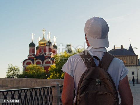 Tourist wearing white cap is exploring Zaryadye park in Moscow, Russia. Uncertain gender. Rear view
