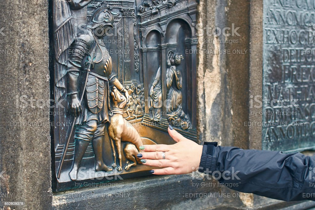 Prague, Czech Republic - September 27, 2014: Tourist is rubbing a bronze plaque of Saint John Nepomuk's dog part of the statue of St. John Nepomuk on Charles Bridge for good luck stock photo