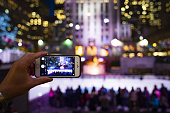 A tourist is taking pictures with his phone at the Rockefeller tower in New York, USA. Rockefeller Plaza is an American Art Deco skyscraper.