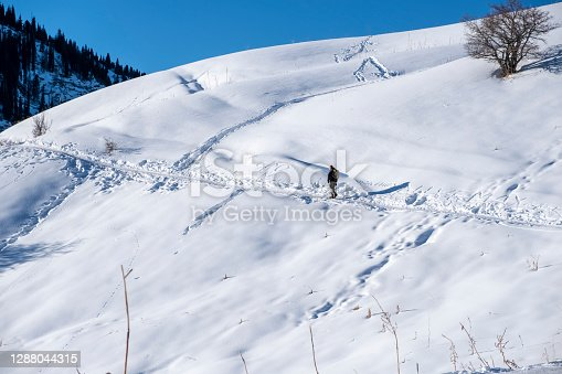 Tourist is walking on trail in mountains in sunny winter day.