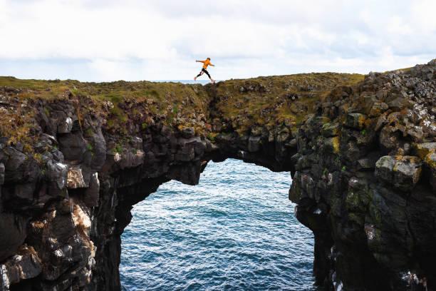 Tourist jumps over a natural rock bridge in Arnarstapi, Iceland stock photo