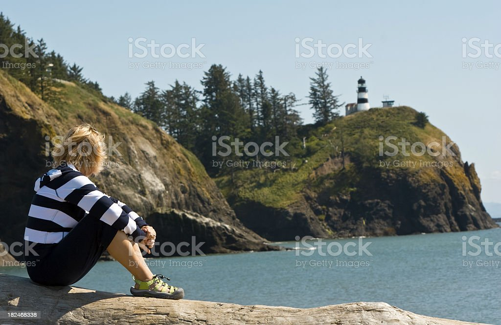 Tourist looking at a lighthouse stock photo