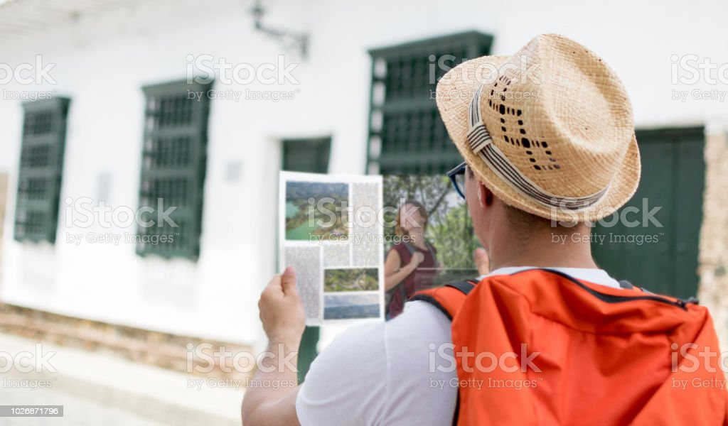 Tourist wearing a hat and backpack looking at a travelling guide....
