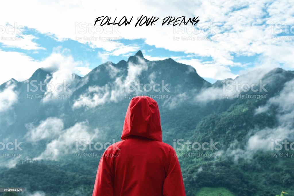 Tourist looking at mountain view with motivation quote stock photo