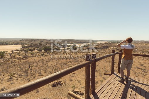 Tourist looking at panorama with binocular from viewpoint over the Mapungubwe National Park, travel destination in South Africa.