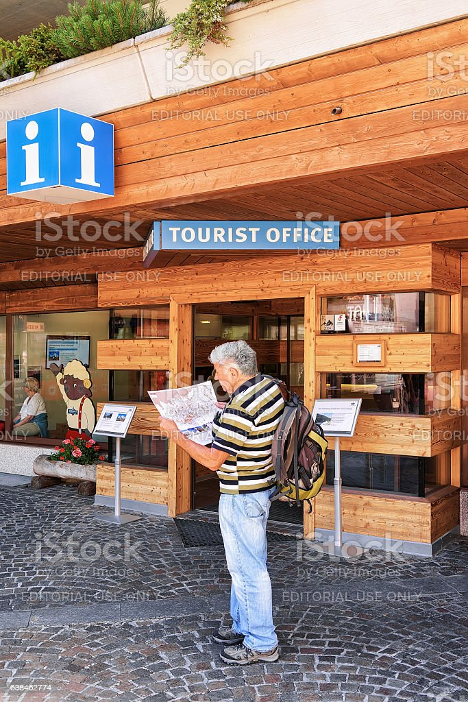 Tourist looking into city map at tourist office of Zermatt stock photo