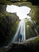 Glyufrafoss waterfall in the gorge of the mountains. Tourist Attraction Iceland. Man tourist in blue jacket standing on a stone and looks at the flow of falling water. Beauty in nature