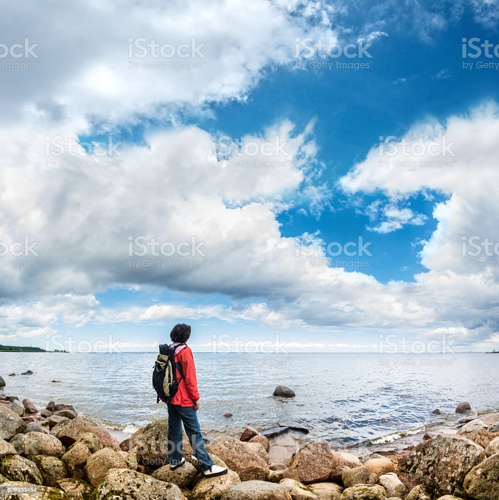 tourist looks into the distance on a background of sea stock photo