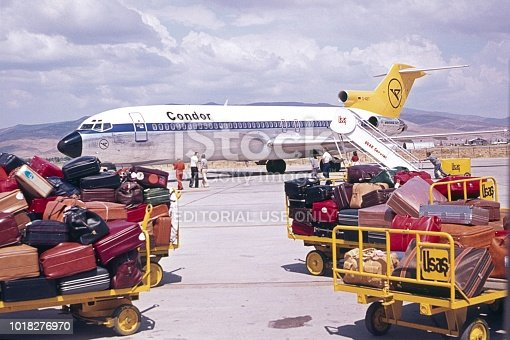 Andalusia, Spain, 1976. Mass tourism. Tourist luggage on an airfield. In the background a charter plane.