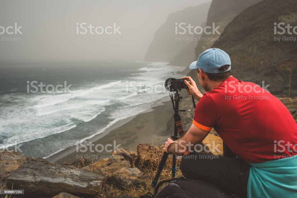 Tourist making photograph of cliff coastline with ocean waves from Cruzinha to Ponta do Sol. Huge mountains on the trekking path. Santo Antao Island, Cape Verde stock photo