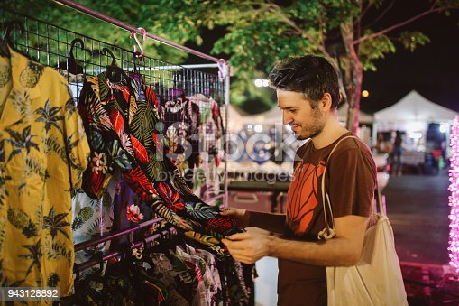 Vintage toned image of a young tourist, browsing the evening street market near Chatuchak in Bangkok, Thailand. Bargain priced clothing, food, and all kinds of stuff for everyday use.