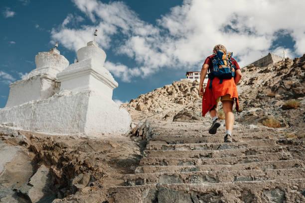 touristischen mann klettert treppen zu tibetischen heiligen ort im himalaya-gebirge - nepal tibet stock-fotos und bilder