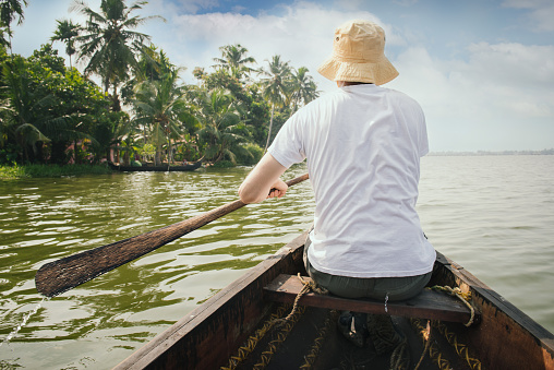 Man traveling to Kerala backwaters, floating on the boat and enjoying beautiful view landscape, Alappuzha, India