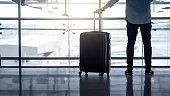 istock Tourist man holding suitcase luggage in airport 1250493291