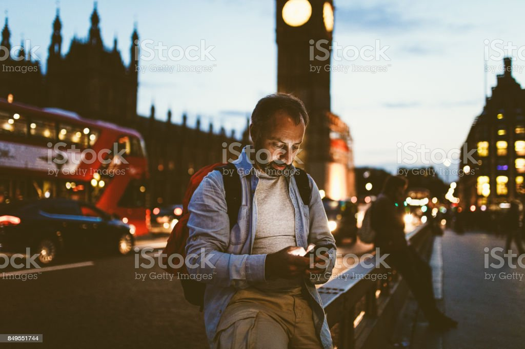 Tourist man in London texting outdoors stock photo