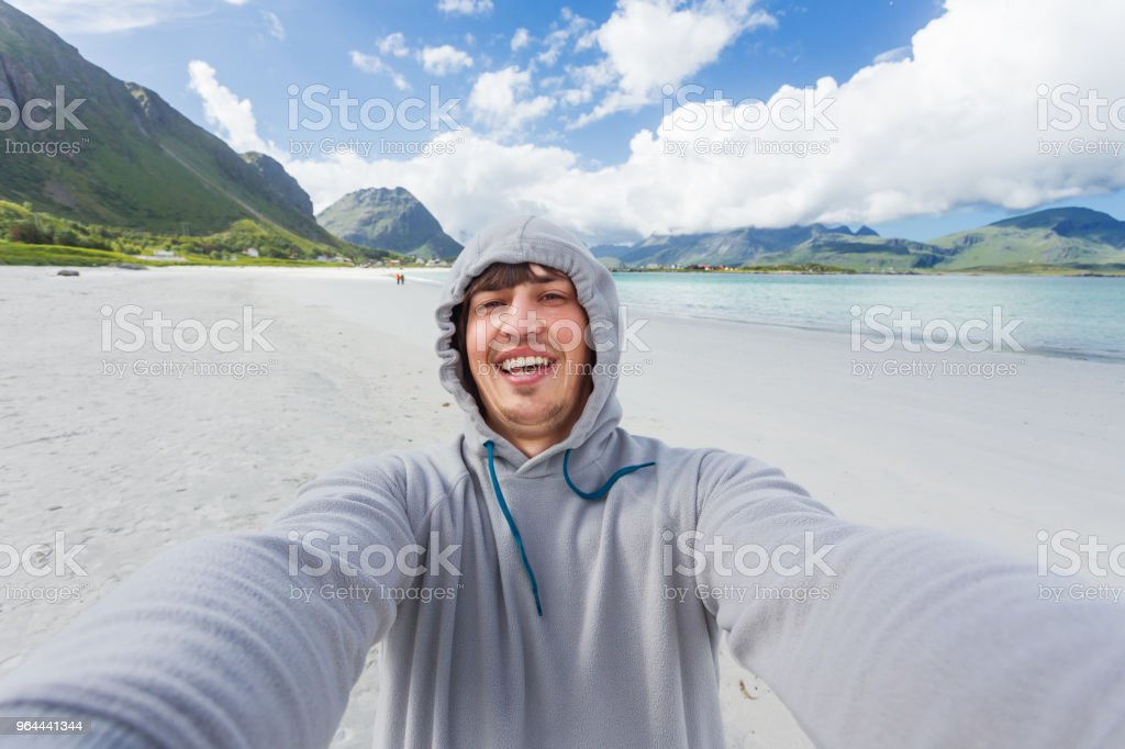 Tourist man making selfie on Rambergstranda beach on Lofoten islands. Beautiful sandy beach and azure water. Norway. - Royalty-free Adult Stock Photo