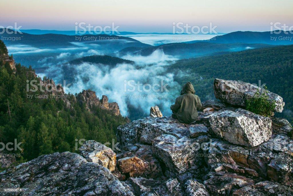 Un turista hombre sentarse en la cima de las montañas y disfrutar de ver la vista del hermoso paisaje de rocas y niebla subiendo en mañana de verano. - foto de stock