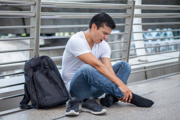 tourist man sitting on floor take off the shoes massaging feet walking a lot of  foot pain after a long walk stock photo