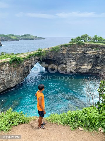 Tourist man standing  on the cliff looking to the an incredibly beautiful beach with beautiful rocks. Aerial  of Broken Beach ,Angel's BillaBong Beach, Nusa Penida island, Bali, Indonesia.