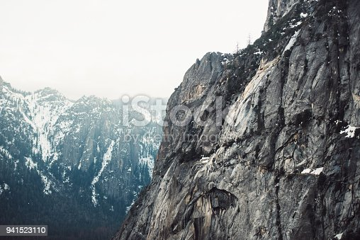 Tourist man standing on the mountain top with backpack and camera and enjoy the view after hiking