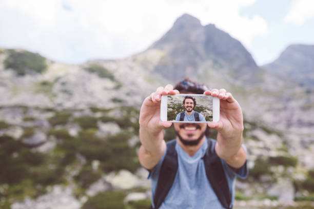 Tourist man taking selfie in the mountain stock photo