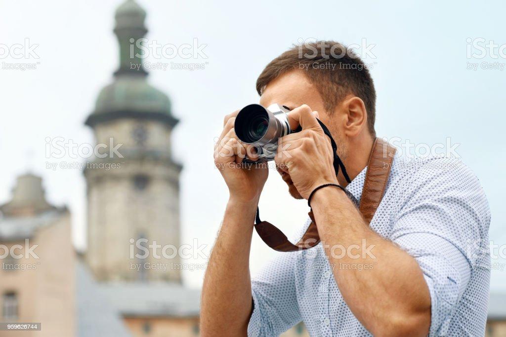 Turístico de hombre con la cámara tomando fotos en la calle. - Foto de stock de A la moda libre de derechos