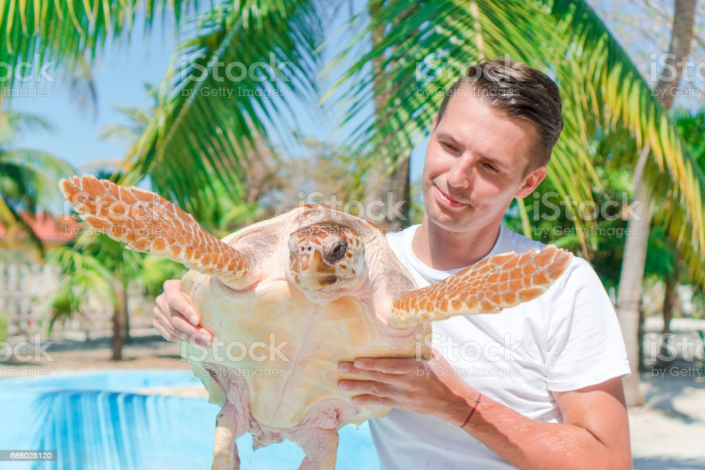 Tourist man with sea turtle in the hands in exotic reserve stock photo
