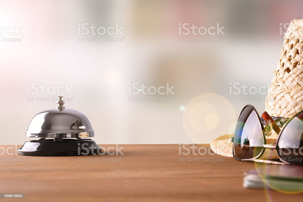 Tourist objects on wood table of hotel reception front view stock photo