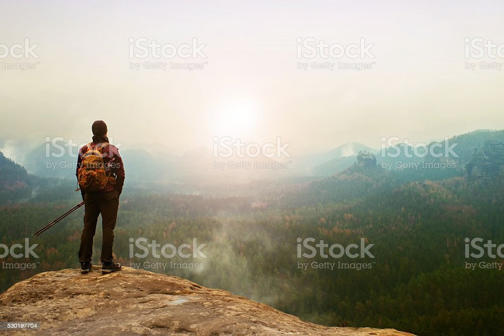 Tourist on cliff watching into deep misty valley bellow. stock photo