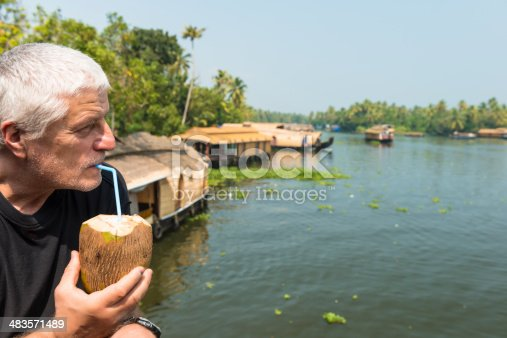 At the side a senior man drinking fresh coconut and observing as many house boats sail down the river in backwaters against palms background and blue sky In Alappey, Kerala, India. Kerala state, with a large network of inland canals earning it the sobriquet