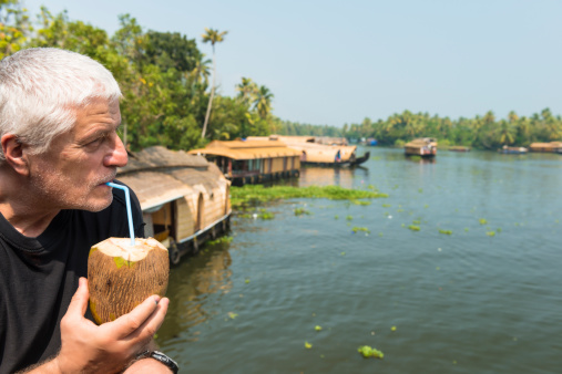 At the side a senior man drinking fresh coconut and observing as many house boats sail down the river in backwaters against palms background and blue sky In Alappey, Kerala, India. Kerala state, with a large network of inland canals earning it the sobriquet \
