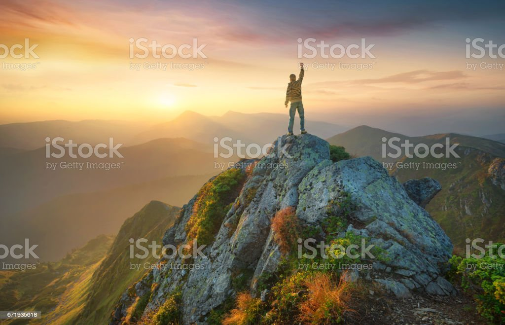 Tourist on the peak of high rocks. Sport and active life concept stock photo