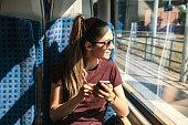 A tourist on the train uses a mobile phone.