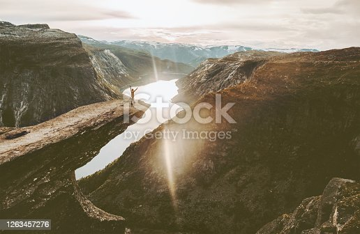 Tourist on Trolltunga cliff edge in Norway adventure travel lifestyle active vacations outdoor sunset mountains   landscape