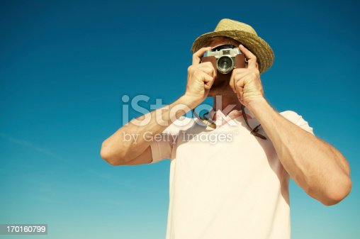 Tourist man in sun hat and pink polo shirt takes a snapshot with an old-fashioned camera