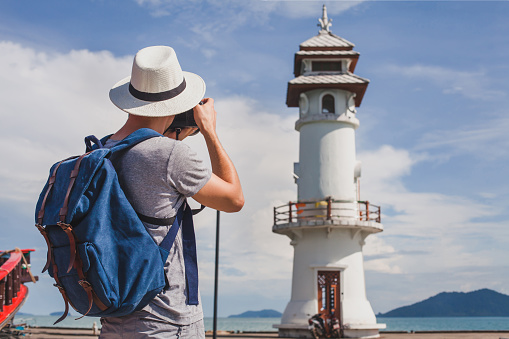 Tourist photographer taking photo of lighthouse.