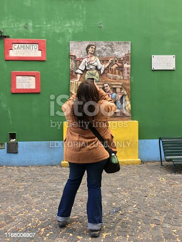 Buenos Aires, Argentina - March 24, 2019: Woman shooting wall in the famous Caminito street in La Boca neighborhood. This is a street museum and a traditional alley full of art showing the common life in this district past