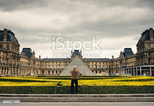 Paris, France - April 25, 2016: Tourist photographing Louvre Pyramid at courtyard of Louvre Museum in Paris. Man is standing in the middle of roundabout at The Place du Carrousel facing pyramid. Building of Louvre Museum in the background.