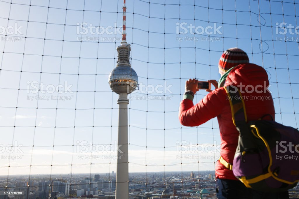 Tourist photographing the TV Tower, Fernsehturm in Berlin stock photo