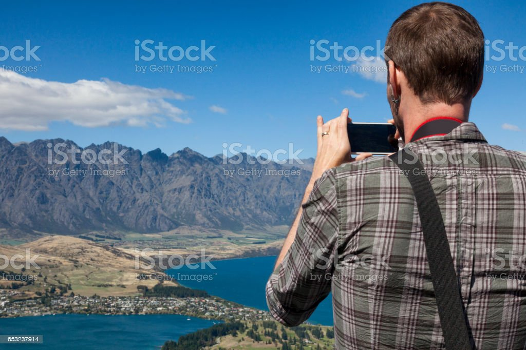 Tourist photographing view of Queenstown in the Remarkable Mountains of New Zealand stock photo
