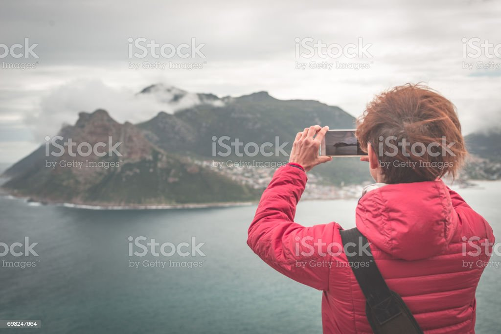 Tourist photographing with smart phone the landscape at Cape Town, on the atlantic coastline of South Africa. stock photo