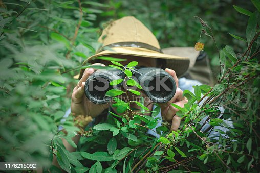 Happy tourist looking through binoculars and hiding in trees.