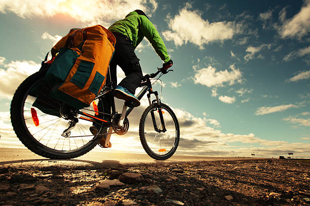 Tourist Bicycle tourist with loaded bike riding on an empty road biking TOUR stock pictures, royalty-free photos & images