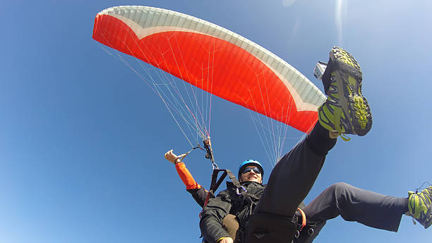 Tourist playing paragliding guided by a pilot Paraglider tandem from below paragliding stock pictures, royalty-free photos & images