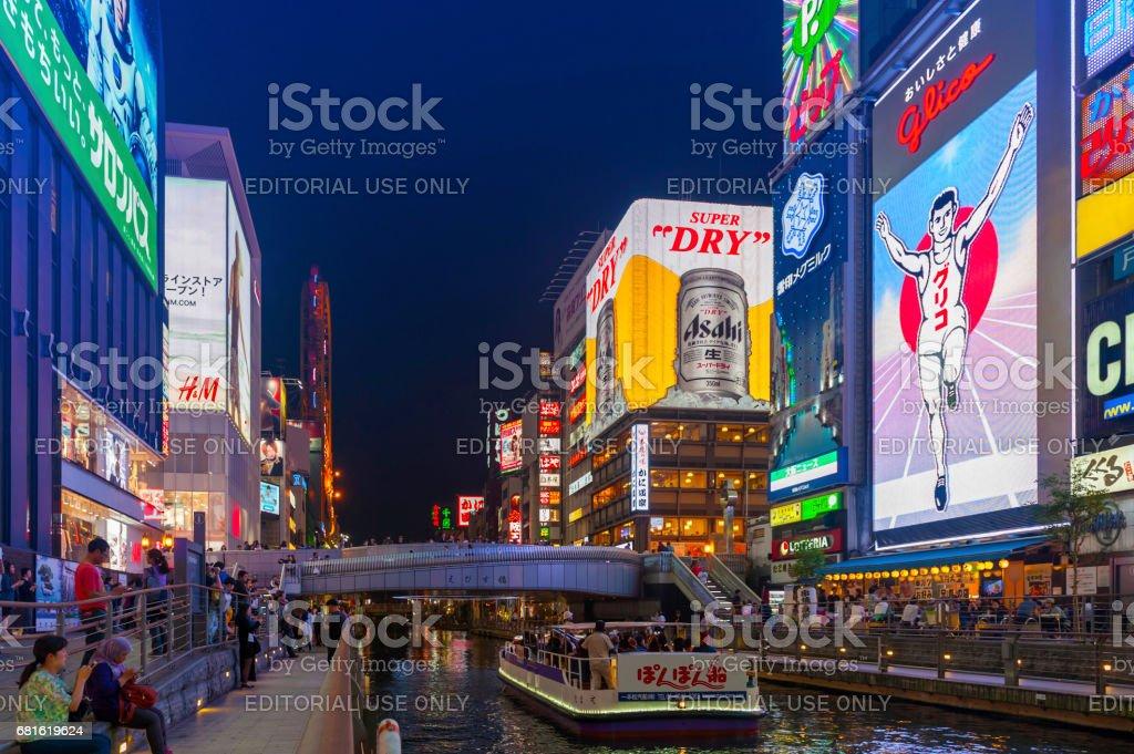 Tourist popular night shopping scene in Osaka City at Dotonbori Namba area with illuminated neon signs and billboards along the river stock photo