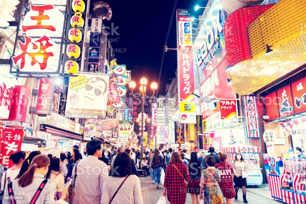 Tourist popular night shopping street in Osaka City at Dotonbori Namba area with illuminated neon signs and billboards alongside stock photo