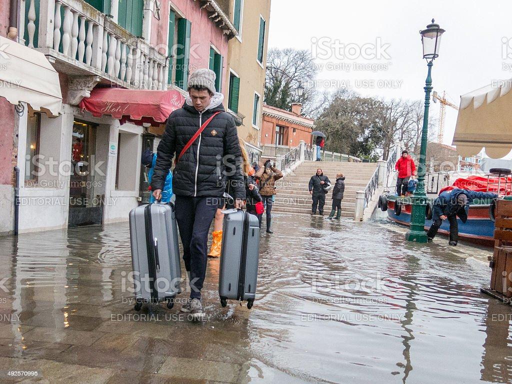 Tourist pulls his suitcases through the acqua alta, Venice stock photo